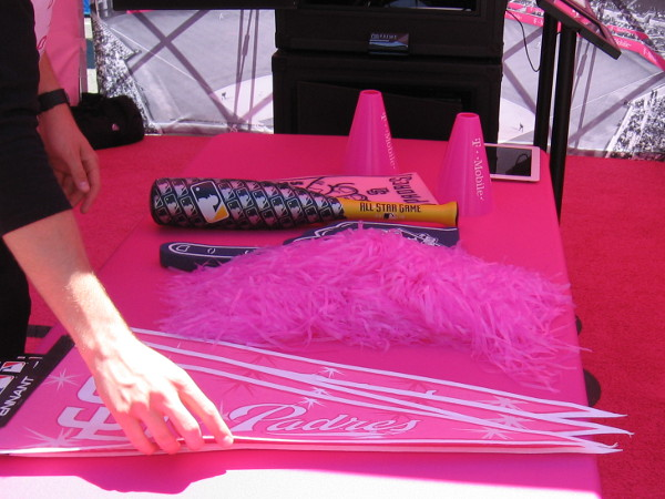 Pink Padres pennants and small All-Star game commemorative bats are placed on a vendor table.