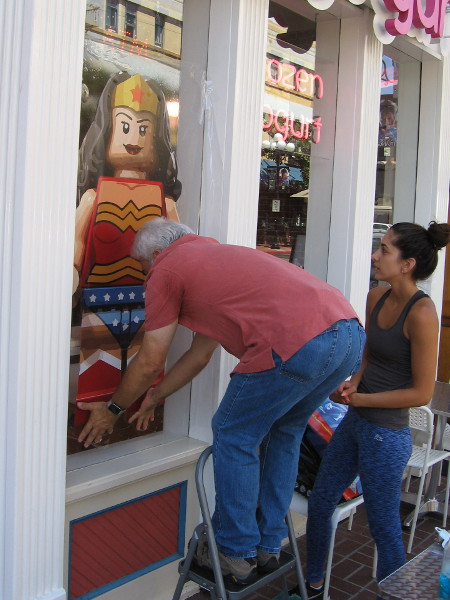 A guy presses Wonder Woman's legs to the window of a yogurt shop.