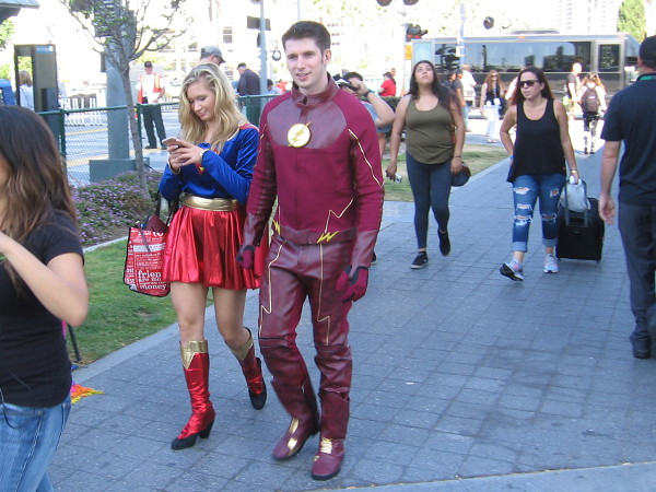I spotted Flash and Supergirl ambling slowly along during San Diego Comic-Con. It appears Supergirl is getting an urgent communication from the Justice League Watchtower.