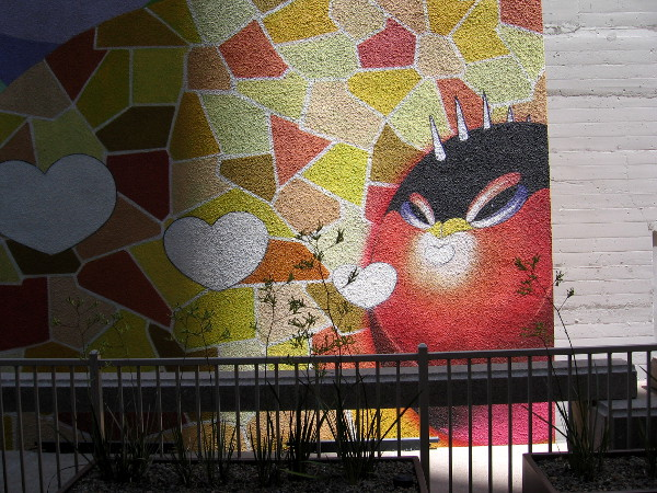 A happy spherical critter with horns blows hearts from the sunlit lower right corner of this awesome mural!