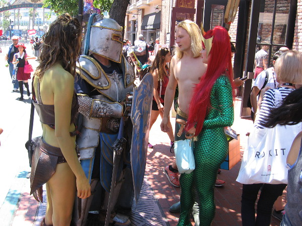 A cosplay Aquaman and Mera have paused to talk to a knight who is accompanied by a green-skinned damsel. Perhaps you can identify the latter two characters.
