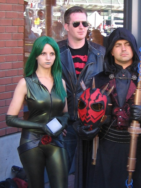 Cosplay enthusiasts stand by during a local television interview outside San Diego Comic-Con.