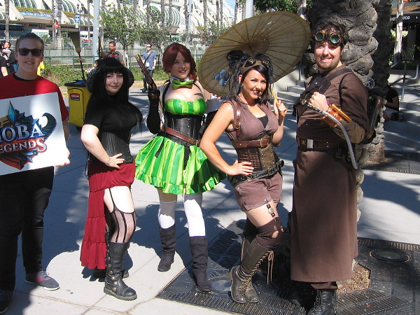 People engaged in cosplay pose for a photo. They are characters from the game Moba Legends.