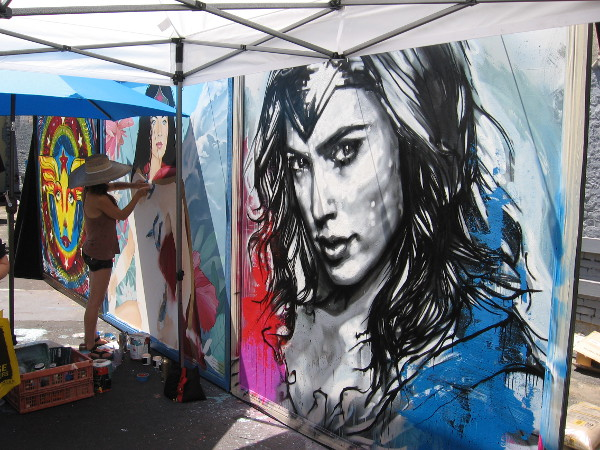 And the right panel, the strong face of comic book heroine Wonder Woman, is being painted by Los Angeles artist Christina Angelina.