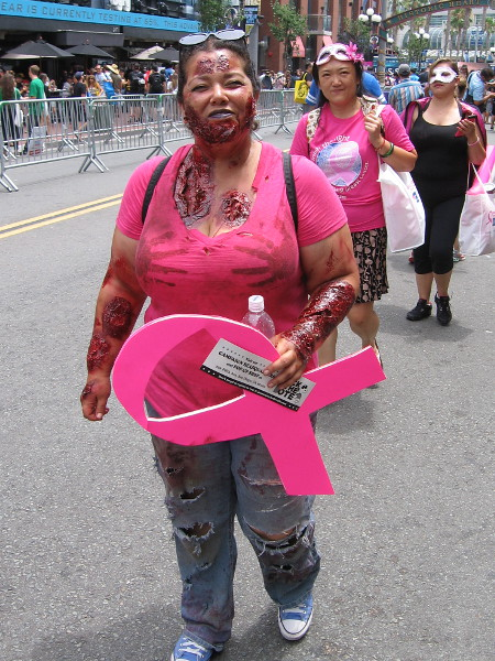 A zombie walks through the Gaslamp with a big pink ribbon. Even the undead can fight for life!