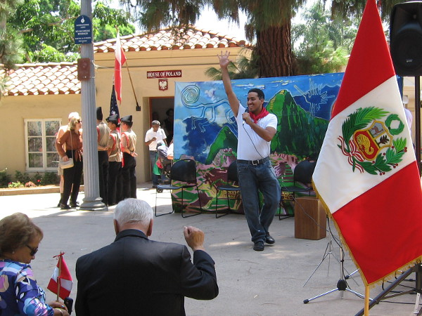 Hearty greetings were offered to everyone attending. Many in the audience had roots in Peru. A mural backdrop depicts Machu Picchu.
