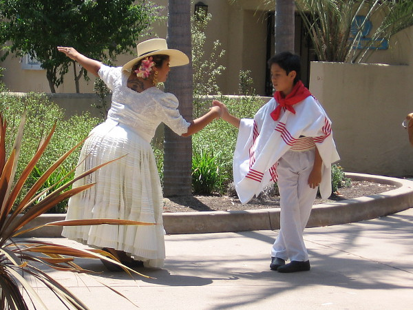 Costumed dancers, young and old, practice off-stage during the festive House of Peru lawn program in Balboa Park.