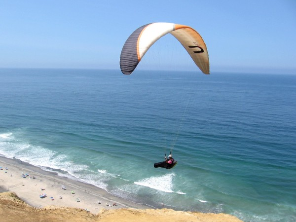 Paraglider high above the Pacific Ocean catches a warm summer updraft created by sandstone cliffs at San Diego's famous Torrey Pines Gliderport.