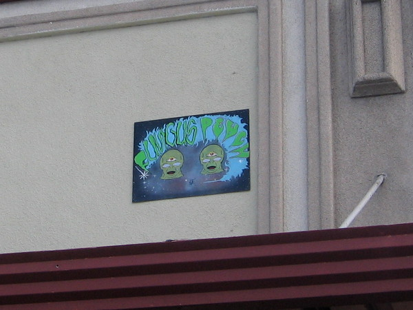 Unusual artwork near a building's rooftop features alien-like creatures with three eyes.