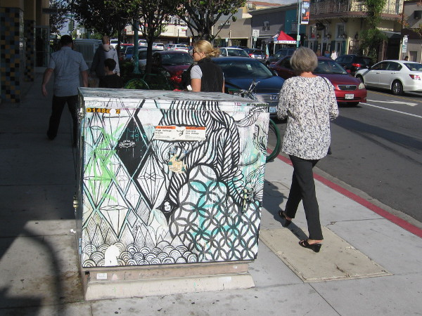 Just walking along the sidewalk, past a creatively decorated transformer box.