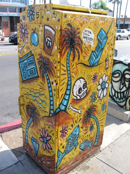 Utility box on 30th Street has tropical palm trees, flowers, fish and a skull.