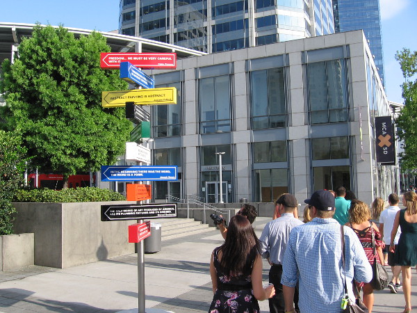 People walk down the sidewalk along Kettner Boulevard. A few glance up at what appears to be a cluster of strangely colorful directional street signs.