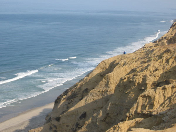 Looking north along the San Diego coast from a point above Black's Beach. A solitary figure looks out at the mighty ocean from atop a weathered sandstone cliff.