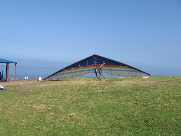 A hang glider is moved on the grassy hill near the Gliderport. Students, instructors and experienced gliders alike must wait for a good, steady wind.