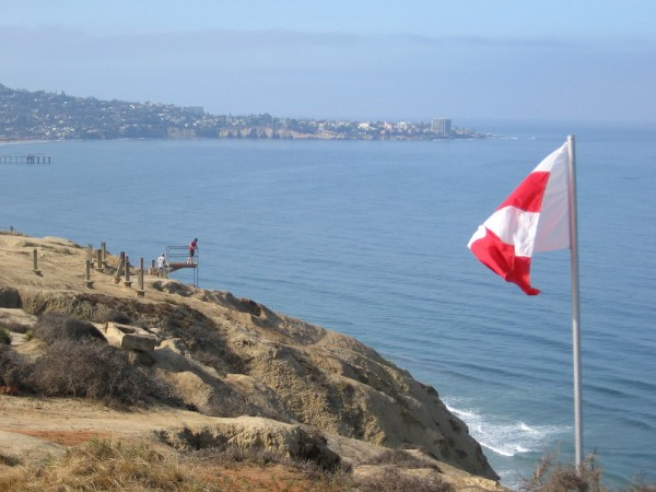 A view looking south from the Torrey Pines Gliderport. Someone stands on the lifeguard perch that overlooks the beach below. La Jolla Cove and a bit of Scripps Pier can be seen in the background.