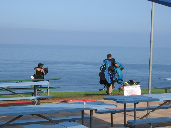 Some activity! Someone wearing a bulky but lightweight paragliding harness sets out across the grass from the patio area at the Torrey Pines Gliderport.