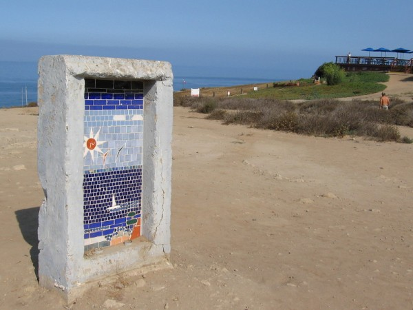 A forlorn concrete monument stands near the dirt parking lot, south of the Torrey Pines Gliderport. On one side a tile mosaic depicts a sailboat and gliders in the sky.