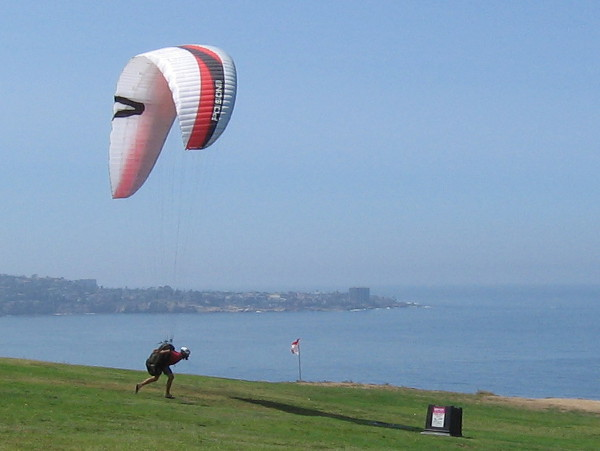Finally! The breeze is pretty good now! The first paraglider is ready to launch! Lift is provided by wind that rises along the long cliffside.