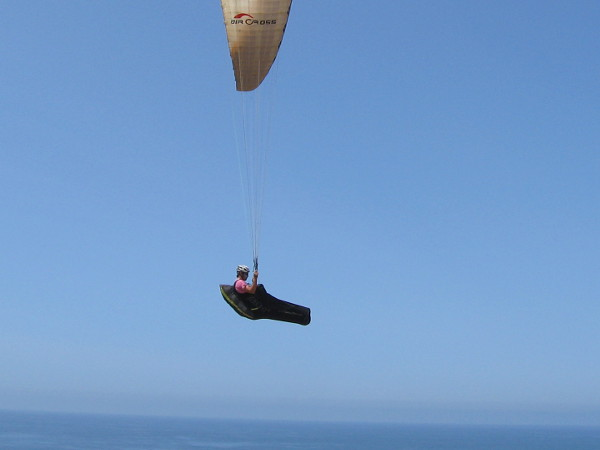 Another paraglider has joined the aerial dance. The lower part of his body is enclosed in a cool-looking pod harness.