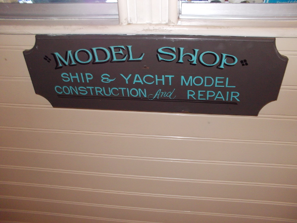 Ship and yacht model construction and repair. Sign beneath a window where museum visitors can watch craftsmen building small works of maritime art.