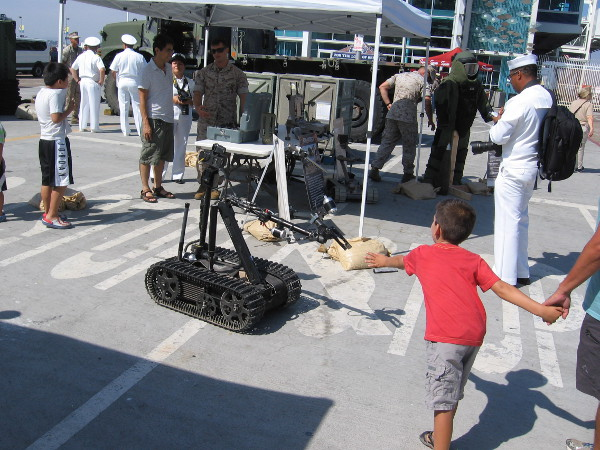 Kid checks out a military robot at the STEM fair on the Broadway Pier during San Diego's 2016 Fleet Week.