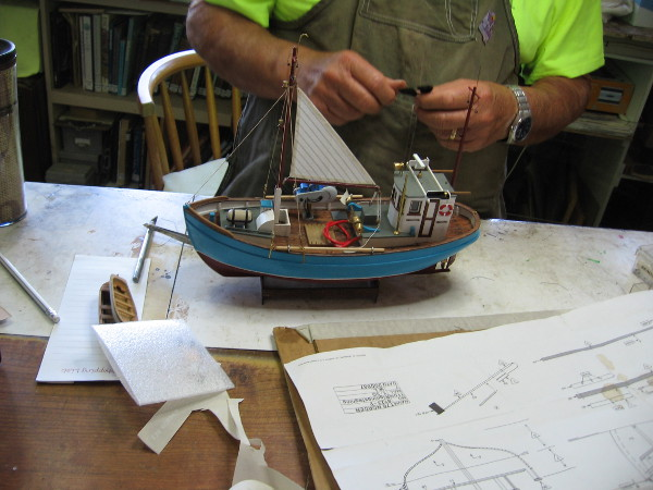 Master craftsman at the Maritime Museum of San Diego is building a small Danish fishing vessel. He works from detailed plans.
