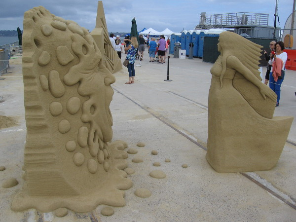 An angry face yells at a graceful woman made of sand.