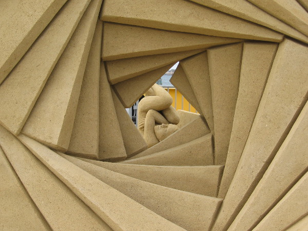 Peering through the amazing layered sand sculpture reveals a human form.