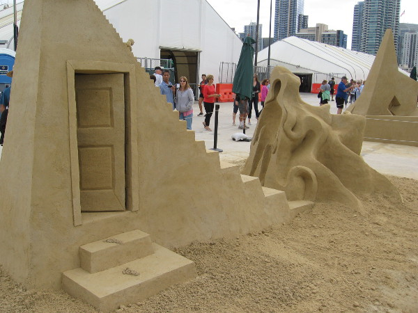 A photo of the rear of this surreal sand sculpture reveals an open door.