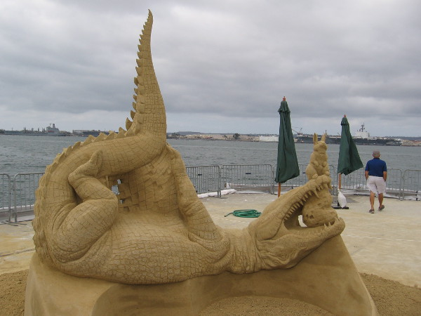 An unusual sand sculpture features a rabbit perched upon an upside-down alligator!