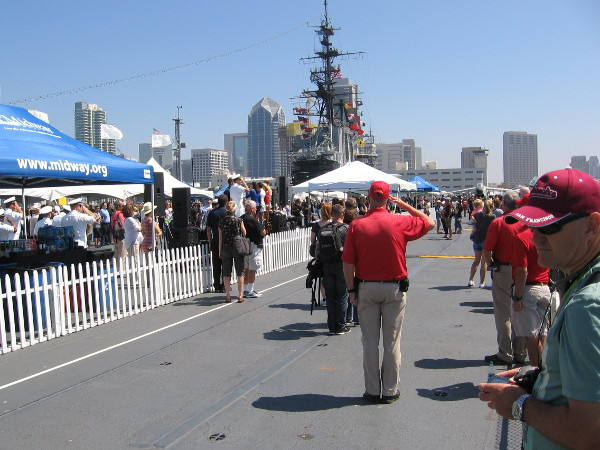 USS Midway Museum volunteer salutes the American flag while the Star Spangled Banner is sung.