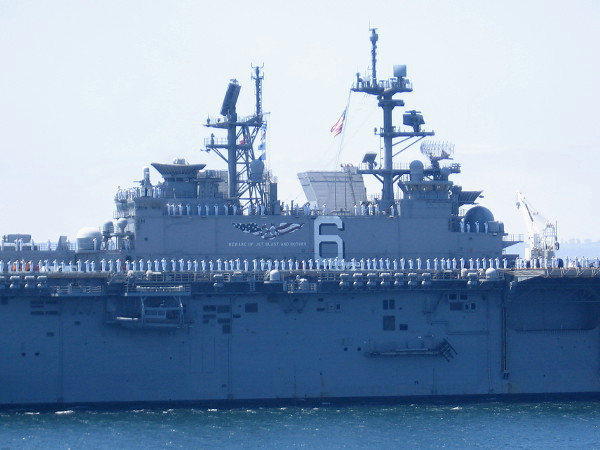 Sailors in white line the deck of USS America as she passes through San Diego Bay during Fleet Week's Sea and Air Parade.