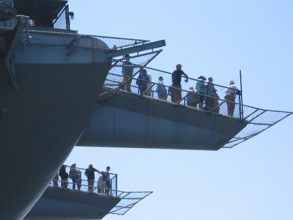 People watch the Sea and Air Parade from launch ramps at the bow of the USS Midway.