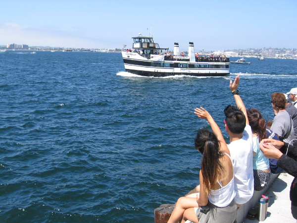 Folks gathered on Navy Pier wave to tourists and others crossing the bay on the Coronado Ferry.
