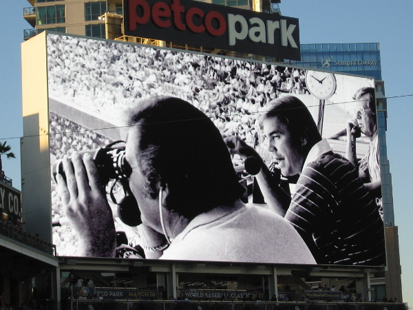 Remembering a sports broadcasting legend. A photo of a young Dick Enberg is flashed on the Petco Park videoboard, celebrating the Padres broadcaster during the 2016 season's final home game.