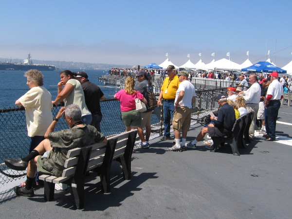 People on the flight deck of USS Midway take in sunshine and military pageantry during Fleet Week in San Diego.