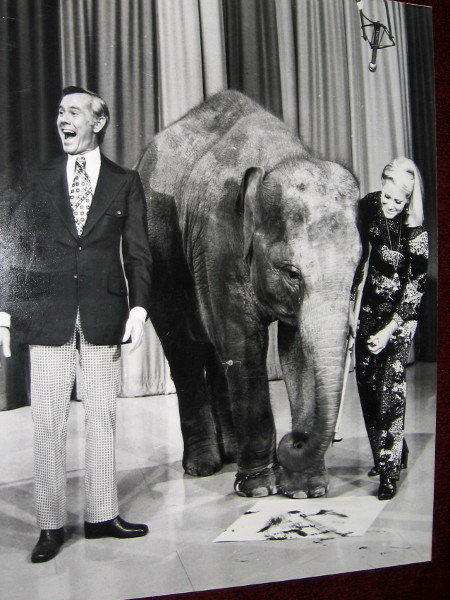 Joan Embery appears with Johnny Carson on the Tonight Show. Carol the Elephant paints on a canvas for the national audience.