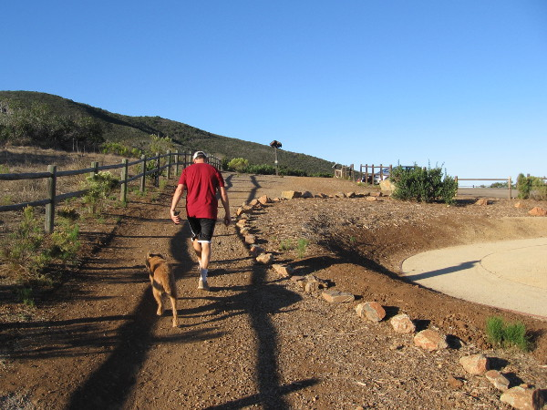 Early morning walker with dog on the Miner's Ridge Loop Trail, across a parking lot from the Trail For All People.