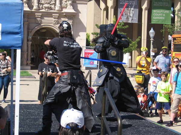 Enthusiasts in cool costumes engage in lightsaber combat as a crowd watches during 2016 Maker Faire San Diego!
