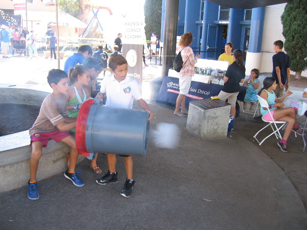 Kids at Maker Faire San Diego test a carbon dioxide cannon, made from a garbage can!