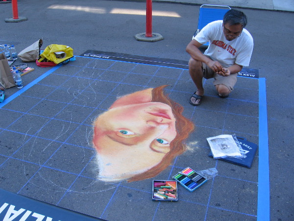 This chalk artist uses a grid to form his emerging creation.