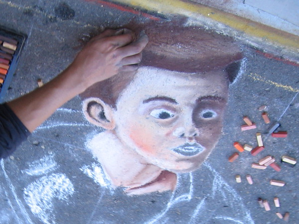 Another face mysteriously materializes on the street. Many different colors of chalk can be used to create subtle effects.