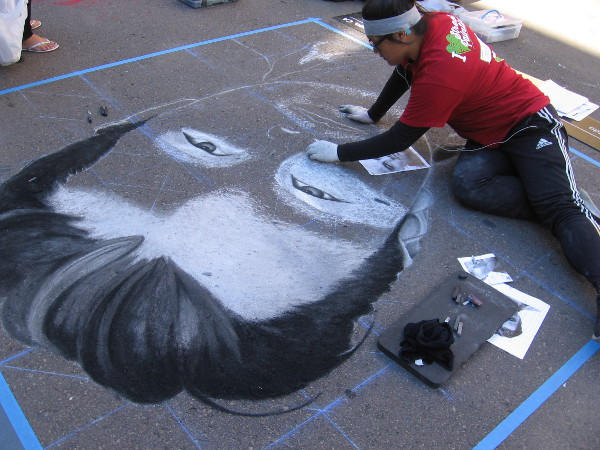 Another chalk artist at work creating a bold face in the middle of the street.