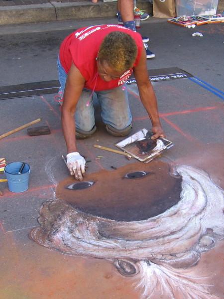 Eyes peer up from the street, regarding a talented chalk artist.