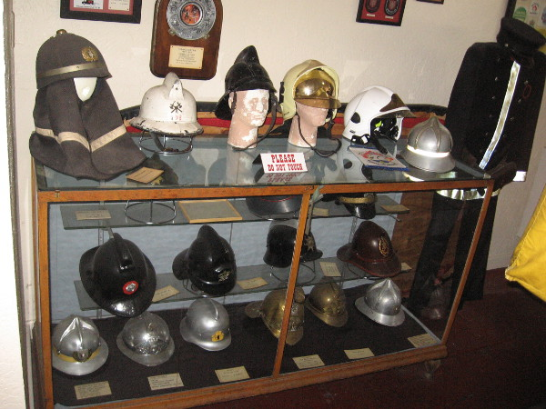 One glass display case in the museum contains all sorts of old fire fighter helmets and protective headgear.