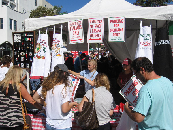 A vendor at Festa sells funny signs and aprons to Italy lovers.
