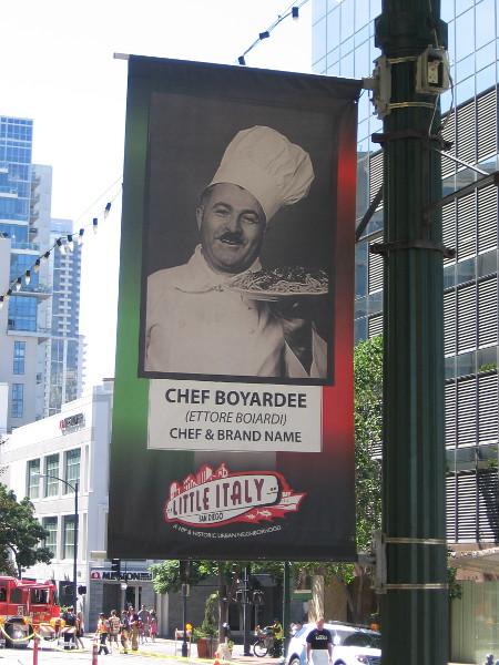 Chef Boyardee (Ettore Boiardi) appears on a street lamp banner in Little Italy.