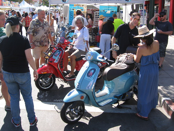 People at Festa check out some shiny new Vespas.
