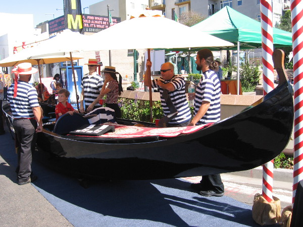 A kid and gondoliers at Festa. Anyone can ride elegant gondolas in San Diego at the Coronado Cays.