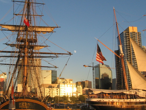 As a nearly full moon rises above downtown San Diego, light from the falling sun reflects from windows and two beautiful Maritime Museum of San Diego tall ships.